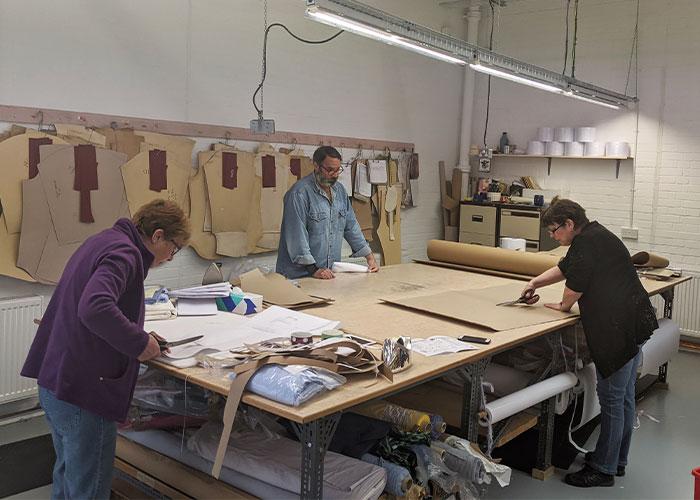 Budd Staff cutting out Covid-19 scrub patterns